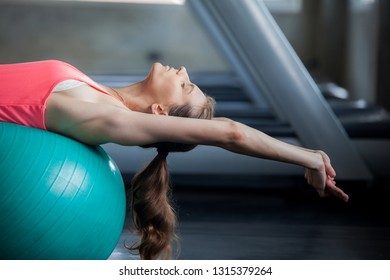 Woman exercising her abs on ball pilates ball  in gym. Fitness concept