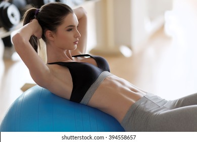 Woman exercising her abs on a Pilates ball. Natural light. Shallow DOF.