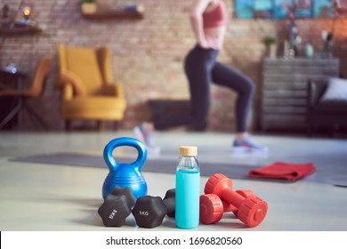 Woman exercising at home. Focus on fitness equipments, barbell and kettlebell. Woman doing walking lunges exercise in the background. Concepts about home workout, fitness, sport and health.