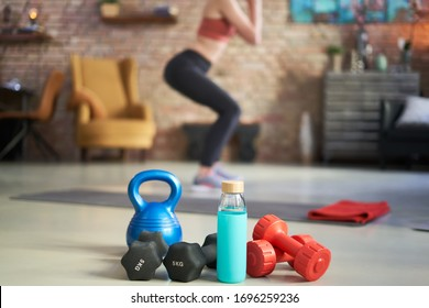 Woman exercising at home in living room, focus on fitness equipments, barbell and kettlebell. Woman doing squats in the background. Concepts about home workout, fitness, sport and health.