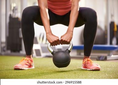 Woman exercising with a kettlebell weight, front view low-section crop