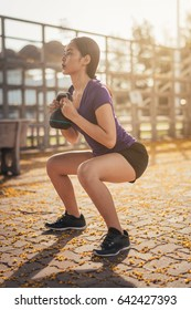 woman exercising with kettlebell while being in squat position.