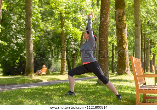 Woman exercising in a lush green spring park working out doing stretching exercises amongst the trees in a side view