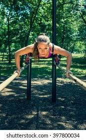 Woman exercising on parallel bars in outdoor gym
