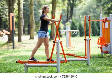 Woman exercising at outdoors gym playground equipment