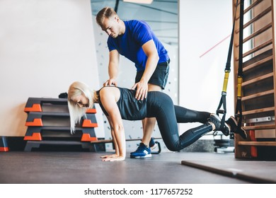 Woman exercising with personal trainer at the gym. Sportive lifestyle. Body shaping.