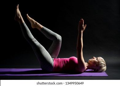 Woman exercising pilates. Dead bug exercise.