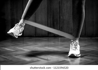 Woman exercising with rubber resistance band at home