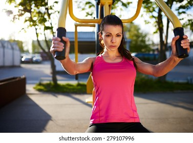 Woman exercising upper body using weights machine outside with serious expression.