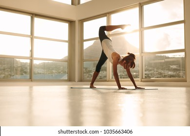 Woman exercising yoga at gym. Female in downward facing dog pose with one leg stretched upward and curled away. Adho Mukha Svanasana pose.