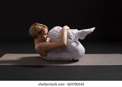 Woman exercising yoga indoors on black background,Yoga -Wind Relieving pose/Pawanmuktasana