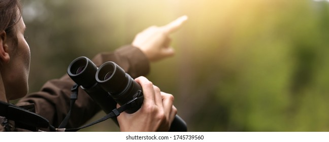 Woman explorer with binoculars showing with finger for animal in the wild forest. Blur dark background. The concept of hunting, travel and outdoor recreation.
