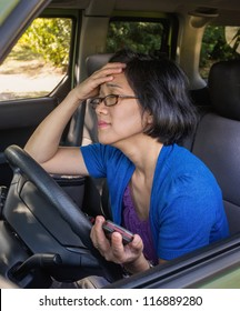 Woman expressing frustration and unhappiness in her car, holding cell phone, in a traffic jam.