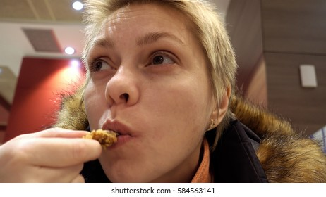 Woman expressively eats chicken in fast food restaurant. Face closeup shot.