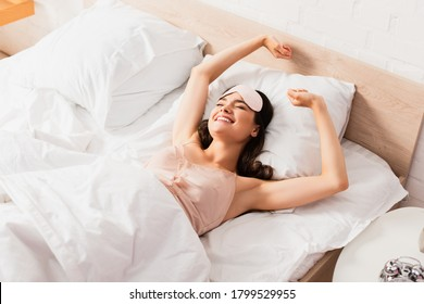 woman in eye mask stretching while lying on bed