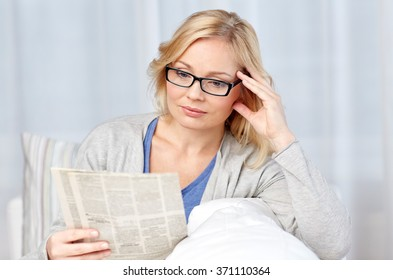 woman in eyeglasses reading newspaper at home