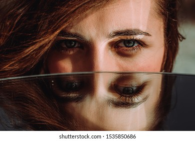 Woman eyes close up reflected in mirror. Hypnotize strong look. Hypnotic deeply penetrating glance. Revengeful insidious expectant gaze. Young caucasian girl face. Horizontal portrait. Good vision