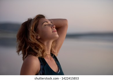 woman with eyes closed and head back enjoying the wind in her hair