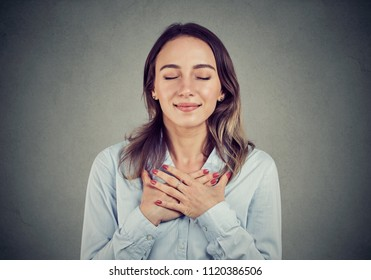 Woman with eyes closed keeps hands on chest near heart, shows kindness, expresses sincere emotions, being kind hearted. Body language feelings concept