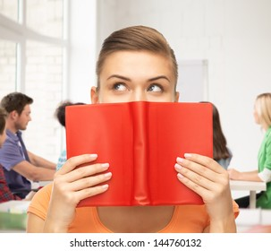 woman eyes and hands holding red book at school