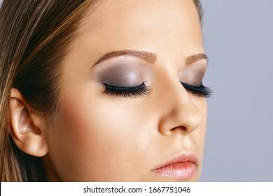 Woman eyes with long eyelashes and smokey eyes make-up. Eyelash extensions, makeup, cosmetics, beauty. Close up portrait