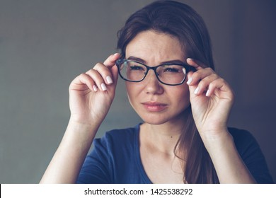 A woman with eyesight problems sees poorly through glasses. Astigmatism concept.