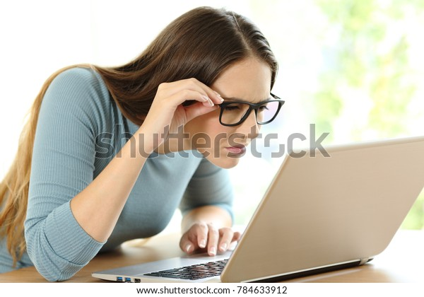 Woman with eyesight problems trying to read on line content in a laptop at home