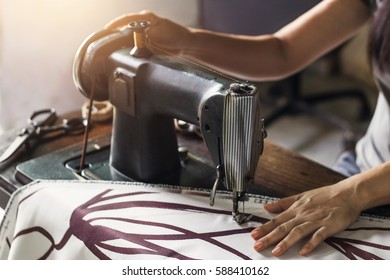 Woman with fabric at vintage sewing machine