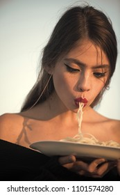 Woman face beauty. Woman eating pasta as taster or restaurant critic. Italian macaroni or spaghetti for dinner, cook. Chef woman with red lips eat pasta. Diet and healthy organic food, italy. Hunger