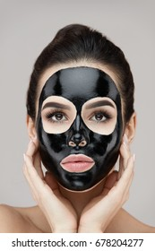 Woman Face With Black Peeling Mask On Skin. Portrait Of Beautiful Young Female Applying Cosmetic Mask On Face. Closeup Of Attractive Girl Model With Skin Care Product On Facial Skin. High Resolution