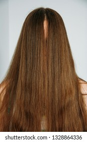 Woman with face closed by long straight hair