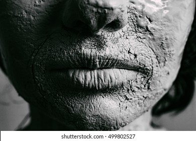 Woman face with cracked skin. Skin of woman is white painted and cracked. Close up on woman's lips. Black and white.