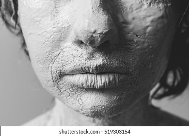Woman face with cracked skin. Skin of woman is white painted and cracked. Close up on woman's lips.