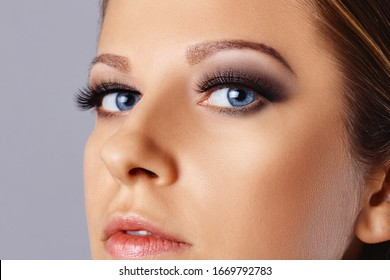 Woman face with eyes with long eyelashes and smokey eyes make-up. Eyelash extensions, makeup, cosmetics, beauty. Close up portrait