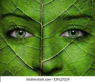 Woman face with leaf texture and green eyes. Ecology concept.