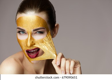 Woman Face Mask. Closeup Beautiful Sexy Girl Taking Off Cosmetic Peeling Gold Mask From Healthy Skin.