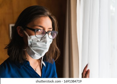 woman with face mask looking out the window