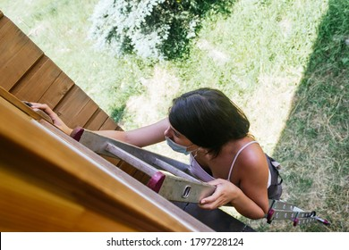 Woman with face mask on a ladder working on a wooden wall with a sander sponge