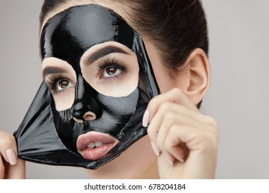 Woman Face Mask. Portrait Of Beautiful Girl Removing Cosmetic Black Peeling Mask From Facial Skin. Closeup Of Attractive Young Woman With Natural Makeup And Cosmetic Peel Mask On Face. High Resolution