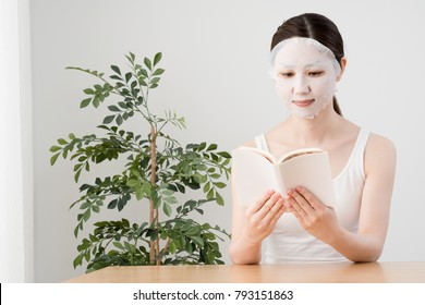 Woman with face mask, reading