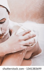 Woman in face mask washing her shoulder with sponge, in bath.