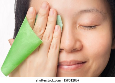 Woman face with oily skin removing oil