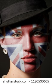 Woman face with painted British flag closeup on black background