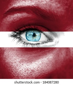 Woman face painted with flag of Latvia