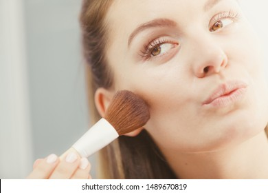 Woman face painting. Girl applying rouge or bronzing powder with brush to her skin in bathroom. Makeup cosmetics and beauty procedures.