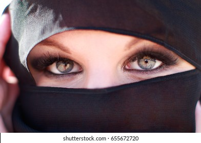 Woman face portrait with deep eyes and eyelashes beauty make up, wearing black scarf niqab hijab around face and neck, photo session in arabic mysterious authentic mystic fairy style, beauty fashion