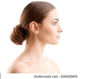 Woman face profile shot. Beautiful young woman with perfect skin looking away while standing at isolated white background.