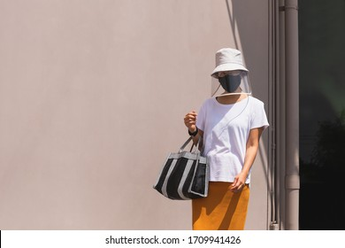 Woman in face shield with hat and protective face mask with hand bag covid-19 spreading outbreak