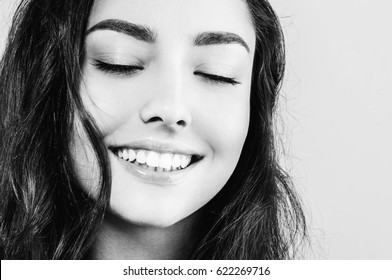 Woman face young beautiful healthy skin and teeth portrait black and white. Studio shot.