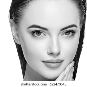 Woman face young beautiful healthy skin portrait with hands black and white. Studio shot.
